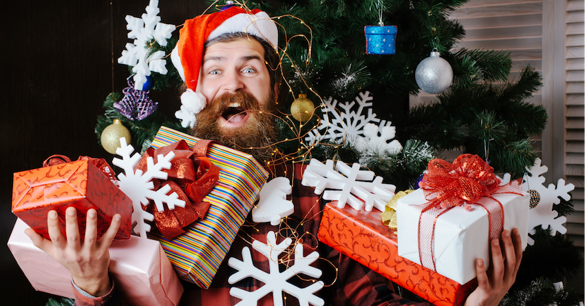 hipster man with beard holding presents in front of christmas tree