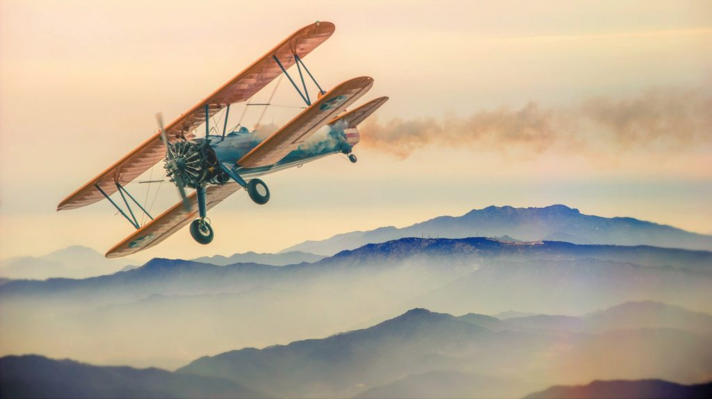 Biplane aircraft in flight above watercolor mountains