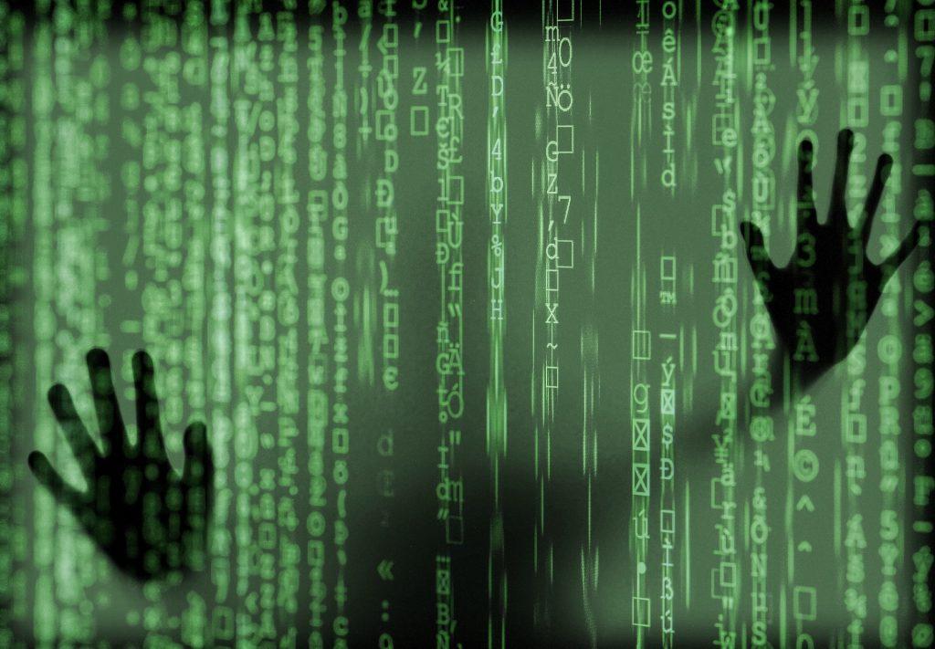 hands behind green code