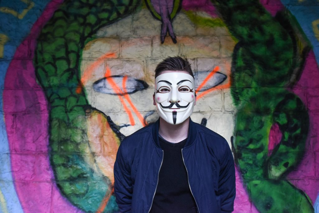 anonymous hacker by graffiti wall