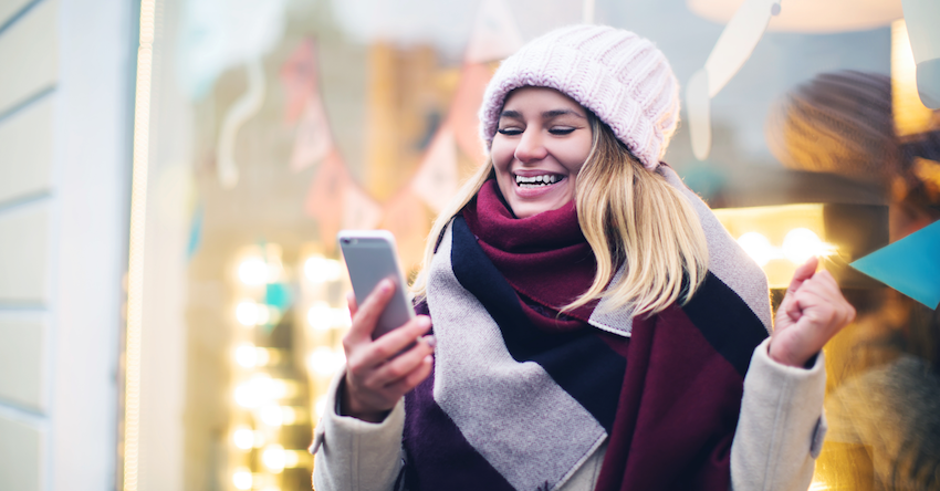 woman with smartphone wearing winter hat