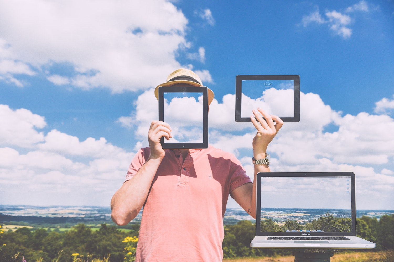 anonymous vpn ad with man covering his face with tablets and laptops in clouds